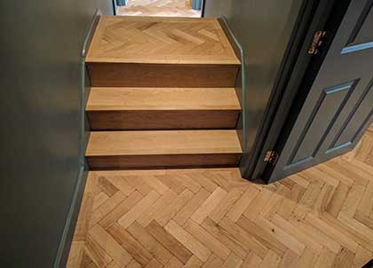 The parquet floor continues up to the top step to link the different levels