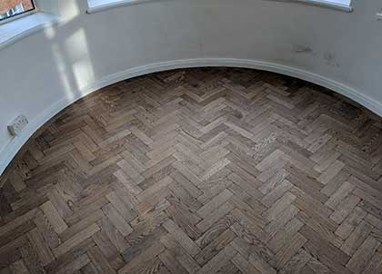The curved skirting provides an interesting contrast to the rigid rectangular parquet blocks which have been laid in a herringbone design