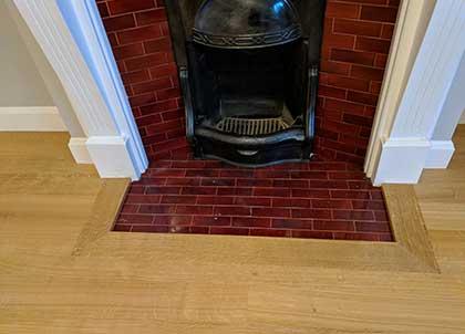 An oak frame sits around the fireplace