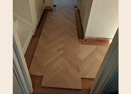 The parquet was fitted in the hall first, the border and tramlines were added at the end