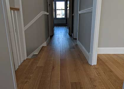 Wood flooring runs seamlessly between the rooms