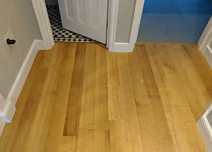 The transition between the oak and tiled floors is completely level