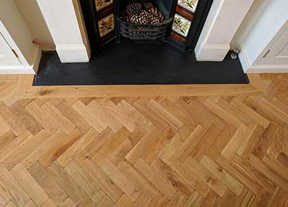 Oak boards match the parquet and frame the fireplace