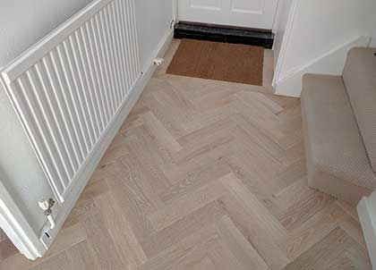 Oak boards in the same pale finish as the parquet blocks are used to create the frame