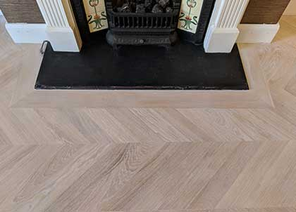 This chevron floor has one small border to frame the fireplace