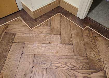 Three toned floor.  Dark parquet flooring, lighter tramline and dark single border