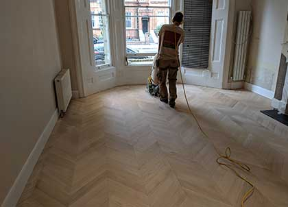 Sanding the parquet for a smooth finish