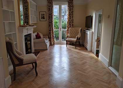 The living room with the bespoke oak parquet herringbone flooring