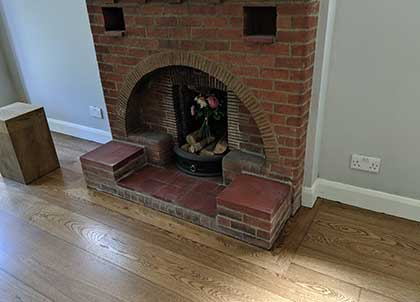 The dark tones complement the red brick fireplace