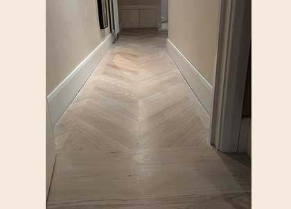 The oak chevron wooden floor runs in the hall and then changes to planks in the bedroom