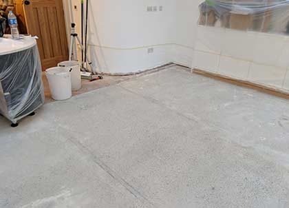 A completely flat surface is needed for parquet, so we had to level out the concrete