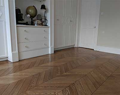 The dark chevron parquet floor looks like it's original to the house