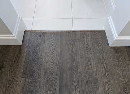 This oak floor runs neatly to the tiled floor. We fitted a thin door trim for a neat finish