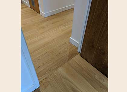 Wooden flooring in the hall runs lengthways, and changes to run towards the window in this adjoining room