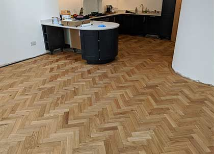 Engineered hardwood flooring installed in the kitchen with its round island and wall