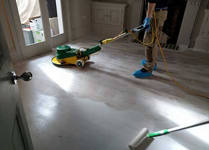 A wooden floor being sealed with a white finish