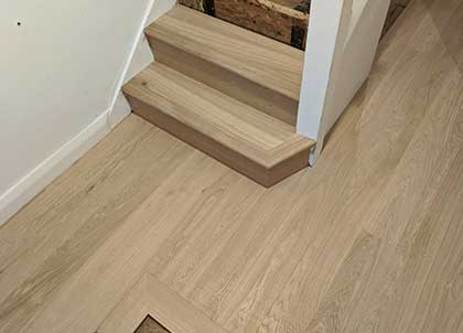 The hall flooring with shaped bottom step