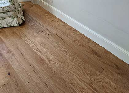 The wood flooring sits under the skirting and allows for the essential expansion gap