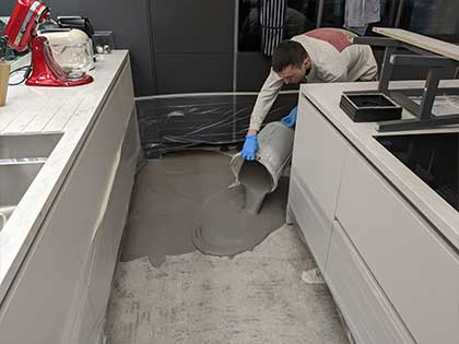 Pouring the specialist self levelling compound to prepare the sub-floor. #CraftedForLife