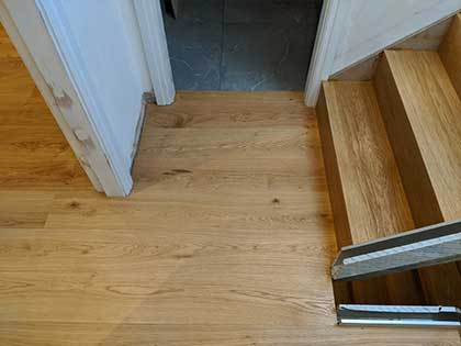 The wooden floor was fitted up to the tiles in the bathroom