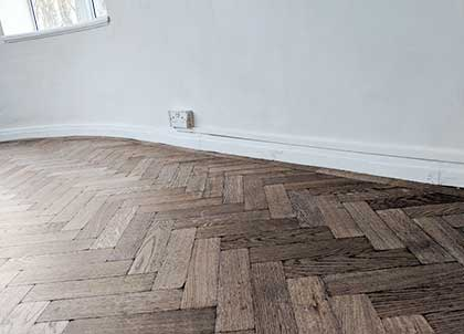 The parquet fits neatly under the original skirting boards