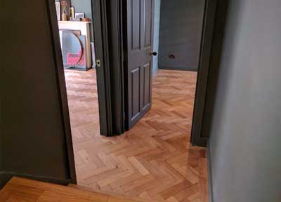 The herringbone parquet pattern has been expertly aligned so it runs seamlessly from the hall into the two adjoining rooms
