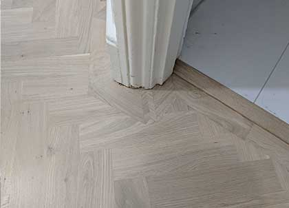 The border of the parquet floor matches the contours of the architrave perfectly